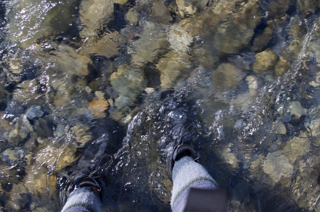 Fording a river in NZ with hiking boots on